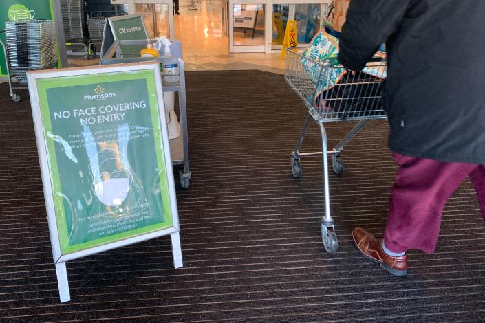 A sign at the entrance informs customers that they must wear a face mask because of the coronavirus pandemic at a Morrisons supermarket in Winsford, northwest England, on January 12, 2021. - People who flout coronavirus lockdown rules are putting lives at risk, the British government said on Tuesday, as cases surge to record highs and rumours swirl of potentially tougher restrictions. Morrisons supermarket chain said customers who refused to wear a mask without a medical exemption will be told to leave its stores, while Sainsbury's said its security staff would challenge shoppers who were not wearing masks. (Photo by Paul ELLIS / AFP) (Photo by PAUL ELLIS/AFP via Getty Images)