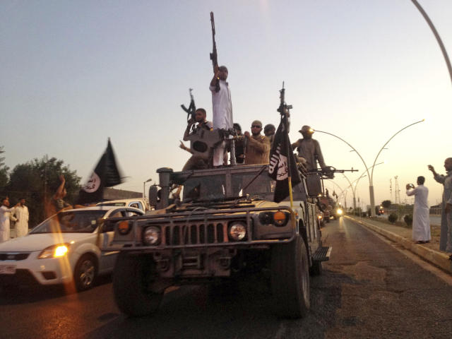 FILE - In this June 23, 2014, file photo, fighters from the Islamic State group parade in a commandeered Iraqi security forces armored vehicle in the northern city of Mosul, Iraq. (AP Photo, File)
