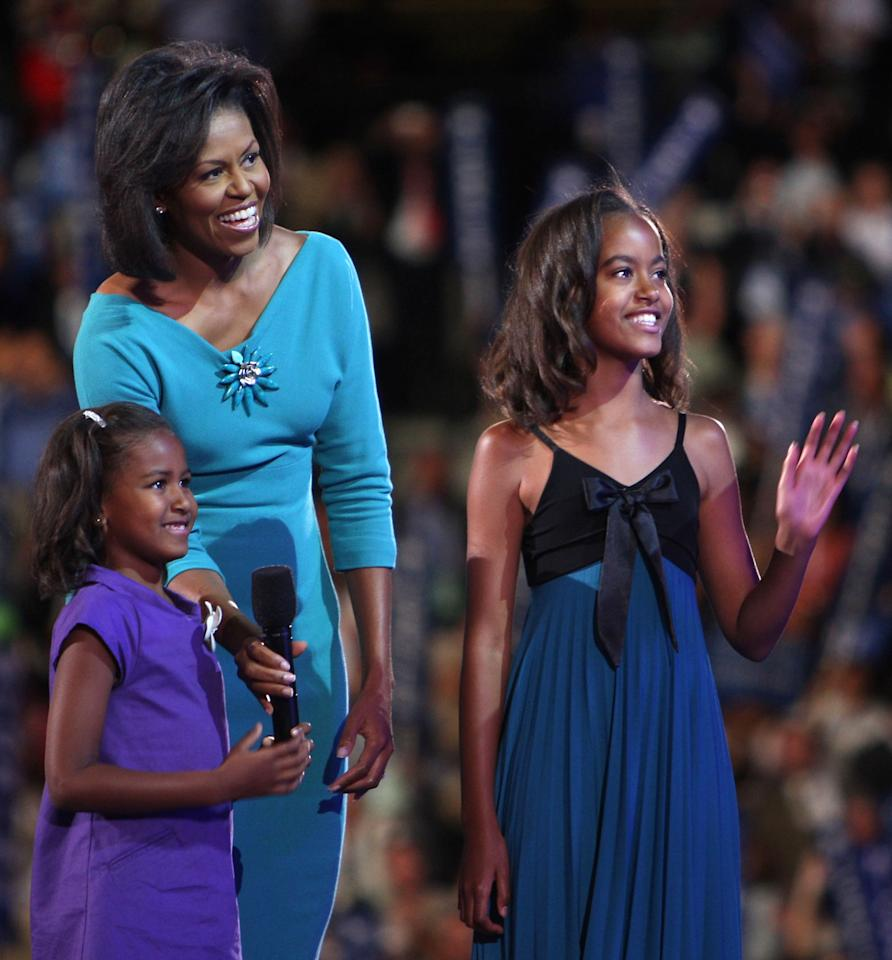 Michelle Obama (C), wife of presumptive Democratic nominee U.S. Sen. Barack Obama (D-IL), stands with her daughters Sasha (L)  and Malia on stage during day one of the Democratic National Convention (DNC) at the Pepsi Center August 25, 2008 in Denver, Colorado. The DNC, where U.S. Sen. Barack Obama (D-IL) will be officially nominated as the Democratic candidate for U.S. president, starts today and finishes August 28th.  (Photo by Spencer Platt/Getty Images)