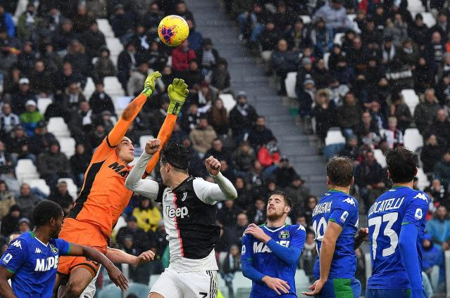 Sassuolo goalkeeper Stefano Turati and Juventus' Cristiano Ronaldo vie for the ball during the Italian Serie A soccer match between Juventus and Sassuolo at the Allianz Stadium in Turin, Italy, Sunday, Dec. 1, 2019. (Alessandro Di Marco/ANSA via AP)