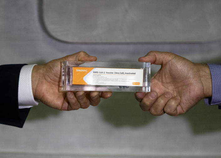 Sao Paulo Governor Joao Doria, left, and Butantan Institute Director Dimas Covas show a box of an experimental COVID-19 vaccine that is being tested in partnership with China's pharmaceutical company Sinovac during a press conference in Sao Paulo, Brazil, Monday, Nov. 9, 2020. (AP Photo/Andre Penner)