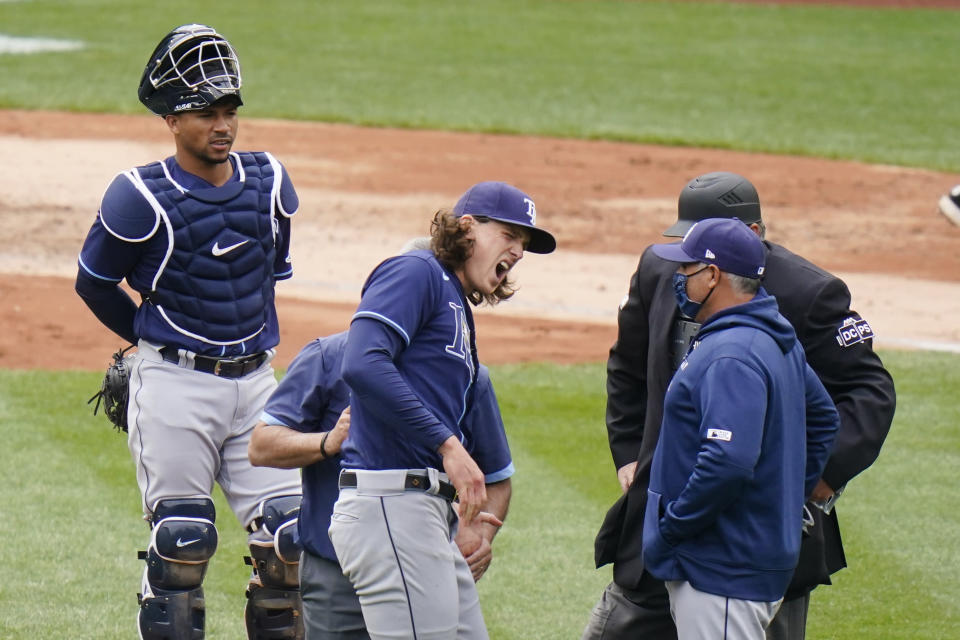 Tampa Bay Rays starting pitcher Tyler Glasnow reacts to pain as a trainer helps him during the fifth inning of a baseball game against the New York Yankees as catcher Francisco Mejia, left, watches Saturday, April 17, 2021, in New York. (AP Photo/Frank Franklin II)