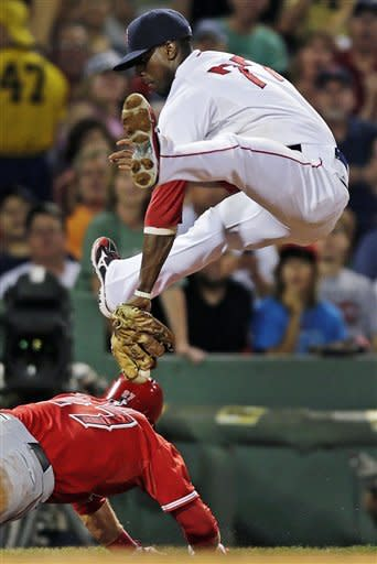 Boston Red Sox third baseman Pedro Ciriaco, top, drops his glove down between his legs as he tries unsuccessfully to catch Los Angeles Angels' Mike Trout diving back to third on a rundown in the third inning of a baseball game at Fenway Park in Boston, Thursday, Aug. 23, 2012. (AP Photo/Charles Krupa)