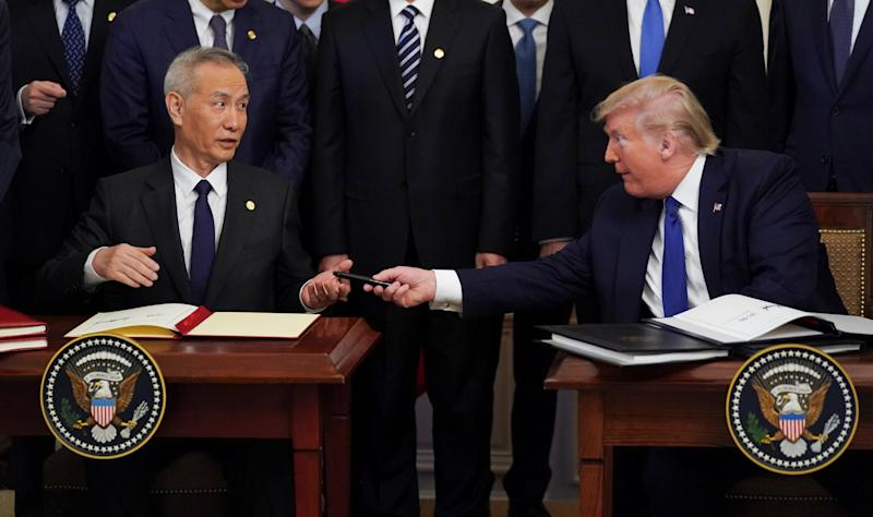"Chinese Vice Premier Liu He is handed a pen by U.S. President Donald Trump after signing ""phase one"" of the U.S.-China trade agreement during a ceremony in the East Room of the White House in Washington, U.S., January 15, 2020. REUTERS/Kevin Lamarque"