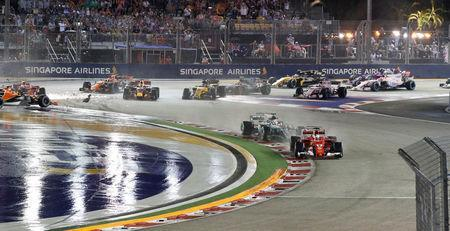 Formula One F1 - Singapore Grand Prix 2017 - Singapore - September 17, 2017 Ferrari's Sebastian Vettel leads Mercedes' Lewis Hamilton at the start of the race as Ferrari's Kimi Raikkonen and Red Bull's Max Verstappen crash out REUTERS/Edgar Su