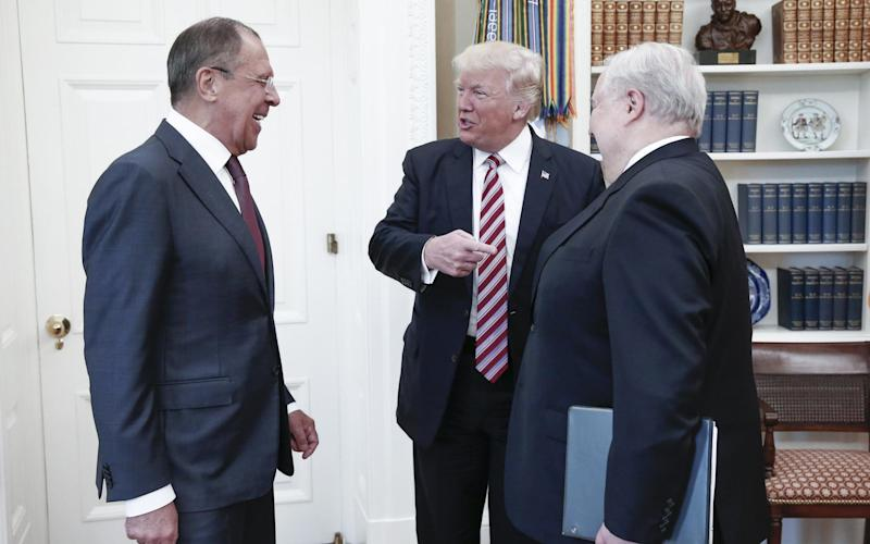Russia's Foreign Minister Sergei Lavrov, US President Donald Trump, and Russian Ambassador to the United States Sergei Kislyak (L-R) talking during a meeting in the Oval Office at the White House.  - Credit: Alexander Shc/Alamy Live News