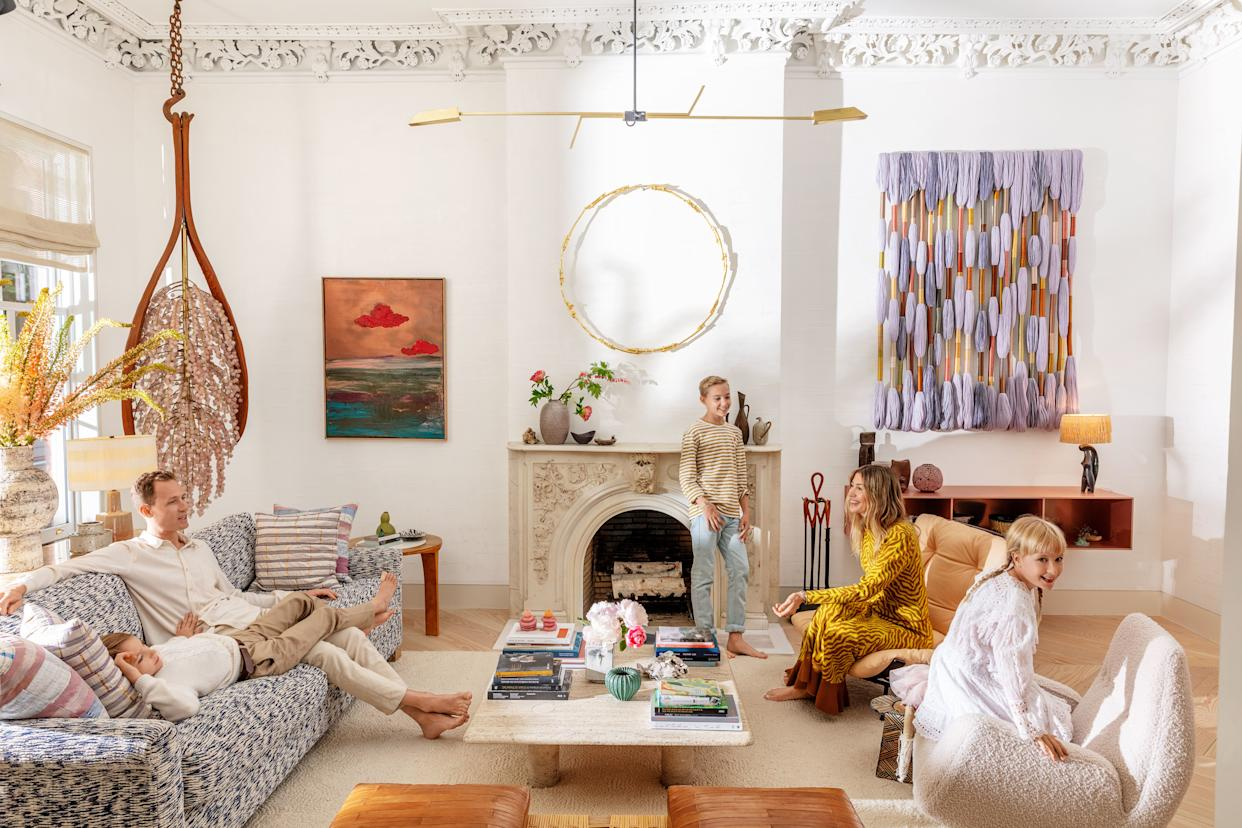 """<div class=""""caption""""> Zach Miner and Johnson with (from left) Asher, Soren, and Agnes in the living room. At far left, a hanging sculpture by Kathleen Ryan; painting by BenoÎt Maire; sculpture above fireplace by Ugo Rondinone; woven wall hanging by Sheila Hicks. </div>"""