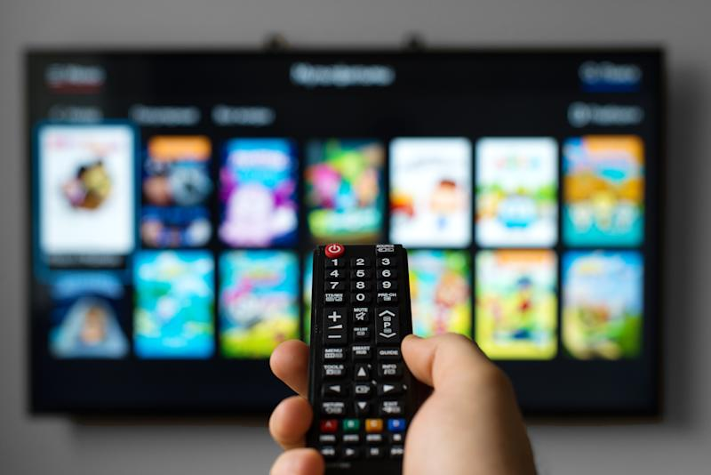 A man pointing a remote at a television showing streaming video options.