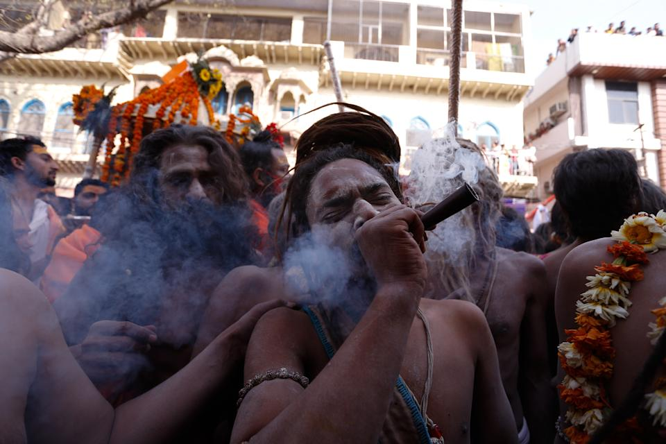 A naga Sadhu or holy man of Juna Akhara smokes weed as others move towards ganges River to take a holy dip on the occasion of first royal bath of Shivratri festival during Maha Kumbh Festival , in Haridwar on March 11, 2021 . (Photo by Ritesh Shukla/NurPhoto via Getty Images)