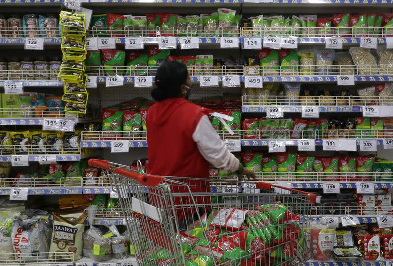 A worker arranges staple goods inside a Reliance supermarket in Mumbai