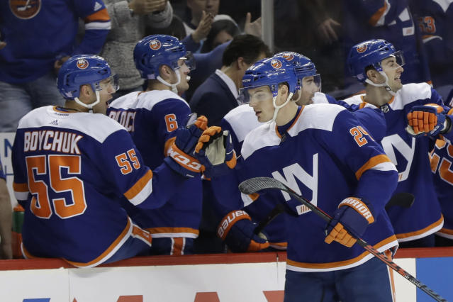 New York Islanders' Scott Mayfield (24) celebrates with teammates after scoring a goal during the first period of an NHL hockey game against the Pittsburgh Penguins Thursday, Nov. 21, 2019, in New York. (AP Photo/Frank Franklin II)