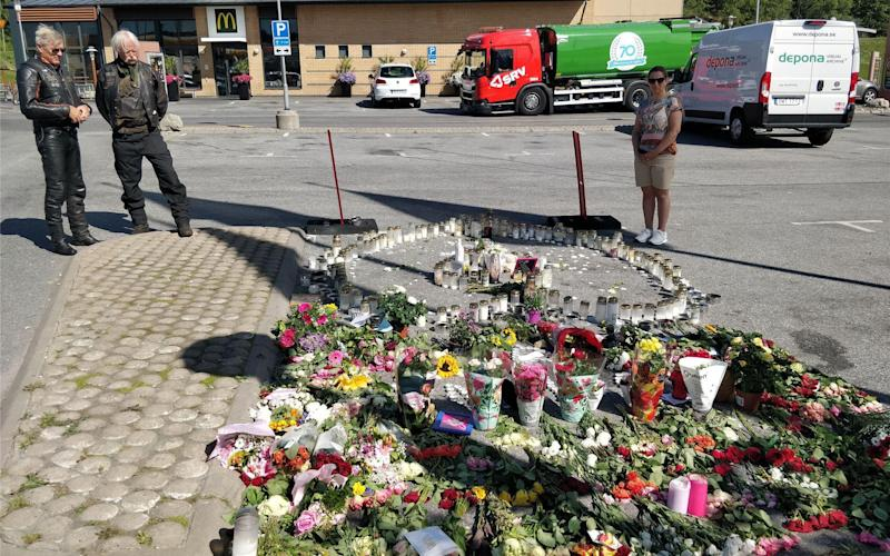 Flowers at the site where a 12-year-old girl was killed after being hit by a stray bullet in a gang shooting at a petrol station car park in Norsborg, south of Stockholm, Sweden - Xinhua / Alamy Live News