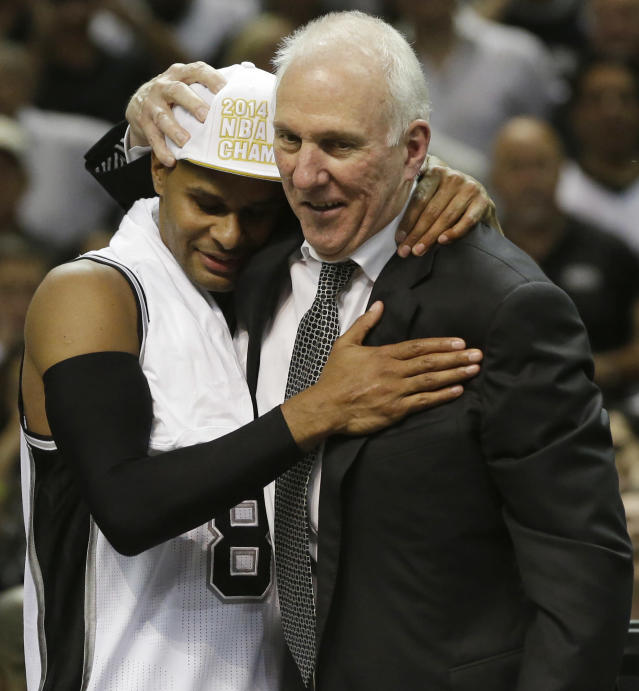 San Antonio Spurs guard Patty Mills (8) and head coach Gregg Popovich embrace after Game 5 of the NBA basketball finals on Sunday, June 15, 2014, in San Antonio. The Spurs won the NBA championship 104-87. (AP Photo/David J. Phillip)
