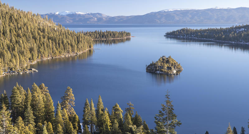 Lake Tahoe is pictured with snow-capped mountains in the distance.