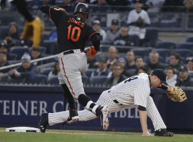 New York Yankees first baseman Neil Walker (14) keeps his foot on the bag for the out after grabbing a wide throw on a ball hit by Baltimore Orioles' Adam Jones (10) during the first inning of a baseball game Friday, April 6, 2018, in New York. (AP Photo/Julie Jacobson)