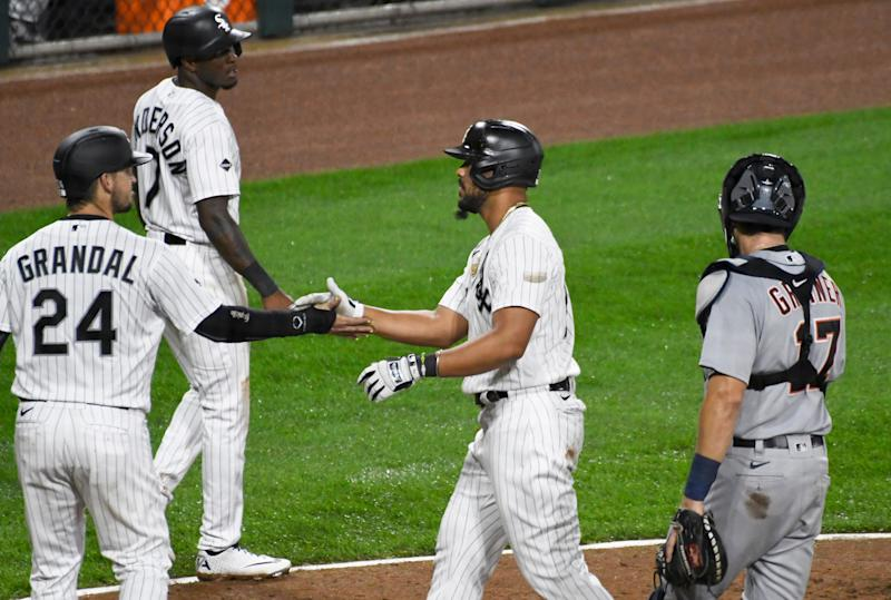 Chicago White Sox's Jose Abreu (79) is greeted by Yasmani Grandal (24) and Tim Anderson (7) after hitting a three-run home run against the Detroit Tigers during the fourth inning of a baseball game, Saturday, Sept. 12, 2020, in Chicago. (AP Photo/David Banks)
