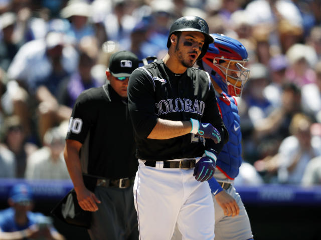 Colorado Rockies' Nolan Arenado reacts after getting hit in the arm by a pitch thrown by Chicago Cubs starting pitcher Cole Hamels in the third inning of a baseball game Wednesday, June 12, 2019, in Denver. (AP Photo/David Zalubowski)
