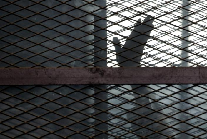 FILE - In this Aug. 22, 2015, file photo, a member of the Muslim Brotherhood waves his hand from a defendants cage in a courtroom in Torah prison, southern Cairo, Egypt. A report released by Amnesty International Wednesday, April 21, 2021, said the number of executions worldwide in 2020 plummeted to its lowest level in at least a decade. But the report said four states in the Middle East — Iran, Egypt, Iraq and Saudi Arabia respectively — topped the global list and pressed on with shootings, beheadings and hangings, ignoring pleas by rights groups to halt executions during the pandemic. (AP Photo/Amr Nabil, File)
