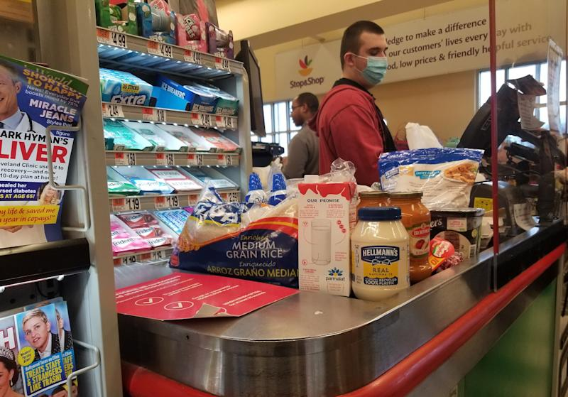Masked cashier rings up purchases behind a plexiglass shield at Stop and Shop grocery store during an outbreak of the COVID-19 coronavirus, Little Neck, Queens, New York City, New York, April 3, 2020. (Photo by Morse Collection/Gado/Getty Images)