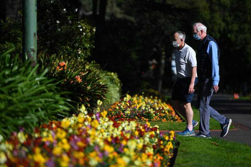 People wearing face masks are seen exercising on the first day of Spring in the Fitzroy Gardens in Melbourne.