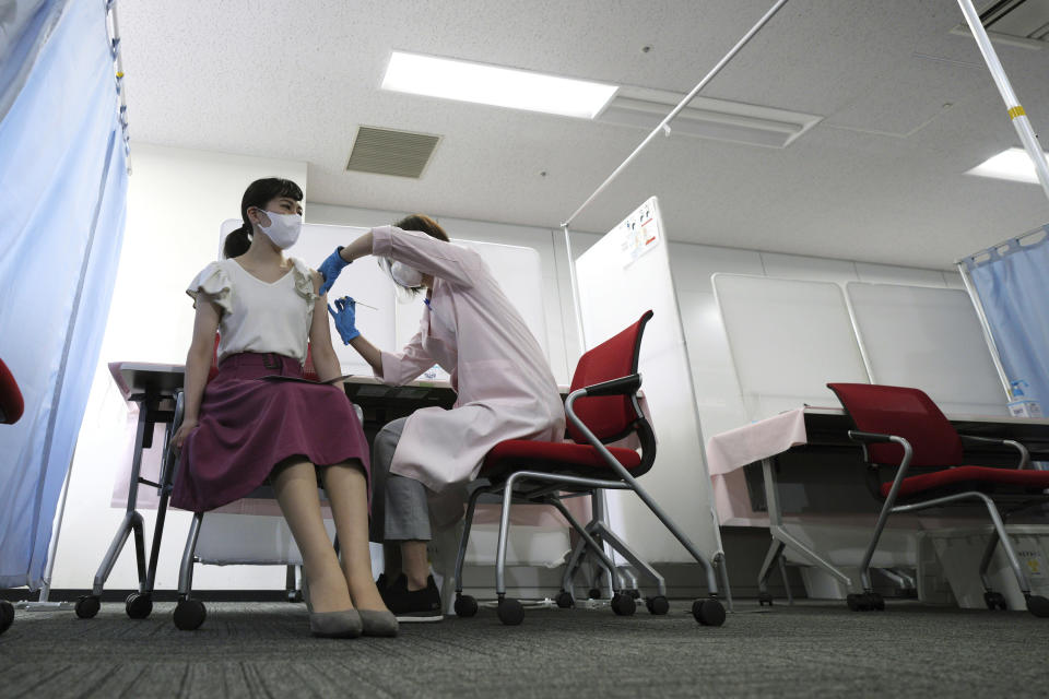 FILE - In this June 14, 2021, file photo, a flight attendant of Japan Airlines takes Moderna's COVID-19 vaccine shot at their office in Haneda Airport as the airline company began its workplace vaccination, in Tokyo. After months of delays due to political and bureaucratic bungling as well as a shortage of vaccines, inoculations in Japan are taking off, and the drive is now racing down to the wire with the Olympics starting in one month. (AP Photo/Eugene Hoshiko, File)