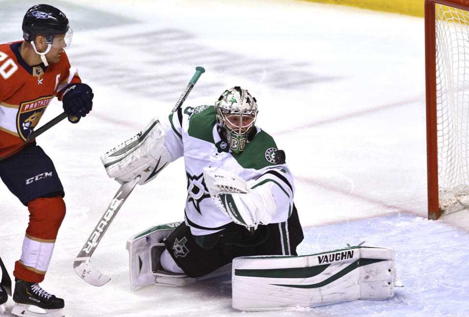 Dallas Stars goaltender Anton Khudobin (35) makes a save as Florida Panthers right wing Patric Hornqvist (70) watches during the second period of an NHL hockey game Wednesday, Feb. 24, 2021, in Sunrise, Fla. (AP Photo/Jim Rassol)