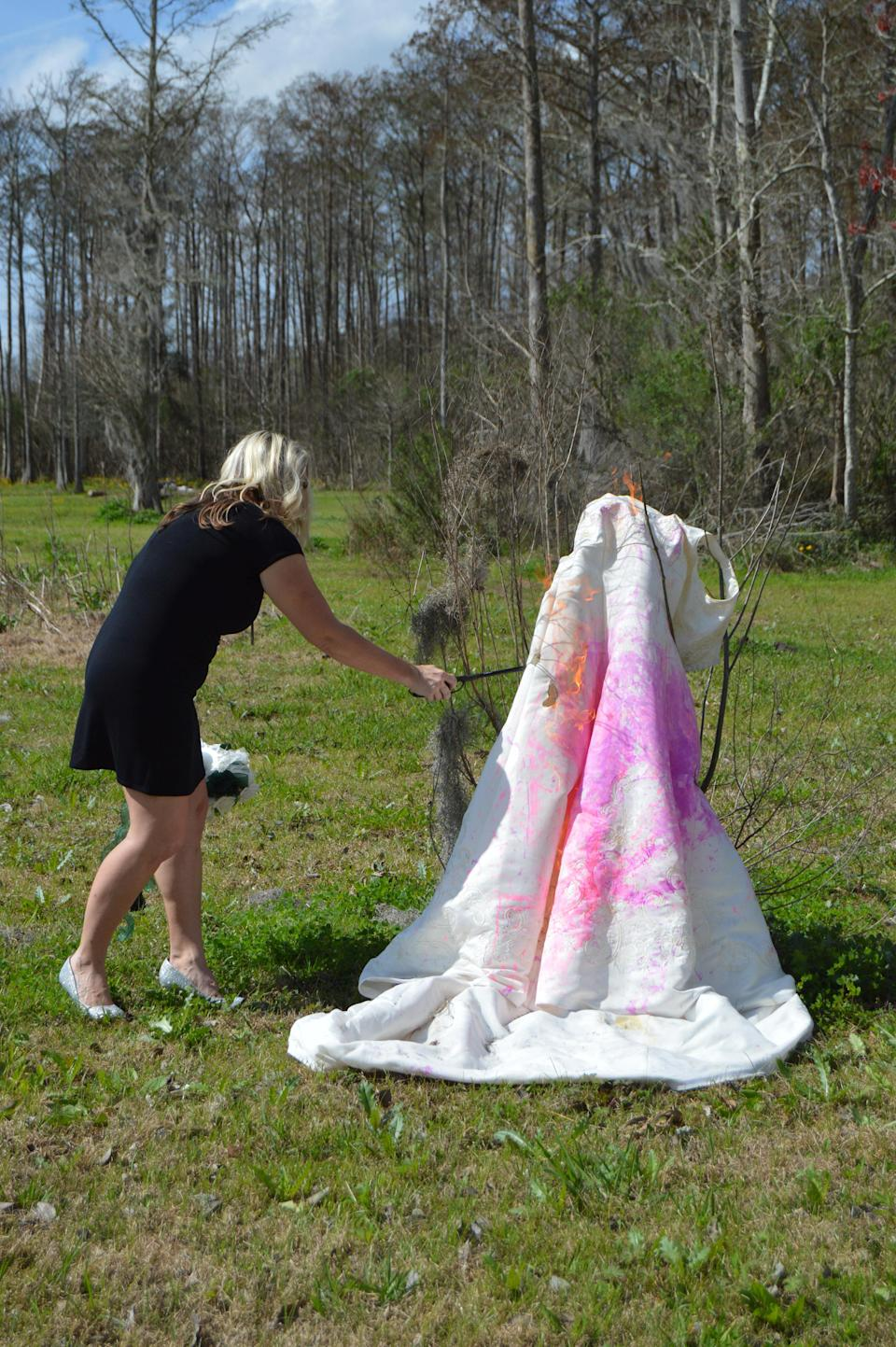 Before torching it, Kristy Scott splattered the gown with paint. (Photo: Caters News)
