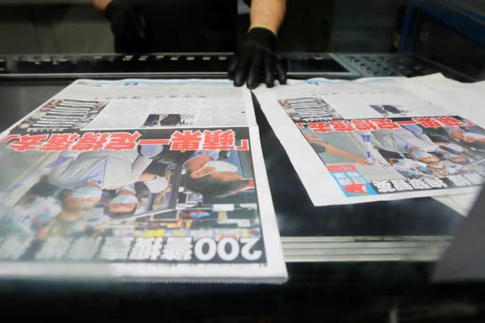 """An employee checks the print quality of copies of the Apple Daily newspaper, published by Next Media Ltd, with a headline """"Apple Daily will fight on"""" at the company's printing facility, in Hong Kong"""