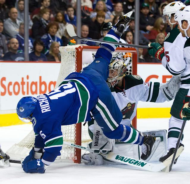 Vancouver Canucks' Brad Richardson, left, is tripped up by Minnesota Wild's Jonas Brodin, back right, of Sweden, in front of goalie Darcy Kuemper during the first period of an NHL hockey game Friday, Feb. 28, 2014, in Vancouver, British Columbia. (AP Photo/The Canadian Press, Darryl Dyck)
