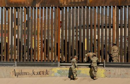 """FILE PHOTO: U.S. soldiers walk next to the border fence between Mexico and the United States, as migrants are seen walking behind the fence, after crossing illegally into the U.S. to turn themselves in, in El Paso, Texas, U.S., in this picture taken from Ciudad Juarez, Mexico, April 3, 2019. The writing on the wall reads, """"Help us Jesus Christ."""" REUTERS/Jose Luis Gonzalez/File Photo"""