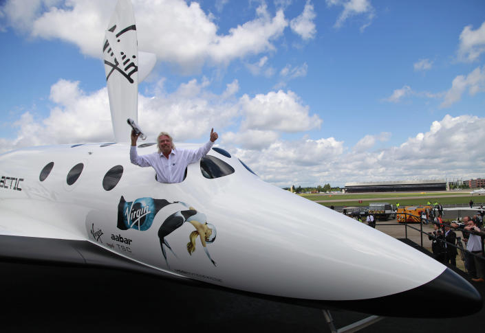 """British billionaire Richard Branson poses for the photographers in the window of a replica of the Virgin Galactic, which according to the company will be the world's first commercial spaceline, at the Farnborough International Airshow in Farnborough, England, Wednesday, July 11, 2012.Virgin Galactic announced """"LauncherOne,"""" a new air-launched rocket specifically designed to deliver small satellites into orbit. Commercial flights of the new orbital launch vehicle are expected to begin by 2016, Virgin Galactic aims to offer frequent and dedicated launches at the world's lowest prices. (AP Photo/Lefteris Pitarakis)"""