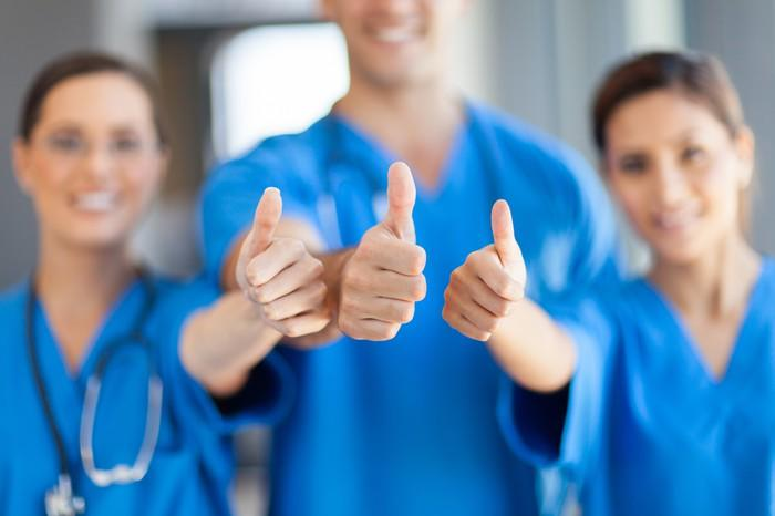 Three healthcare workers with their thumbs up.