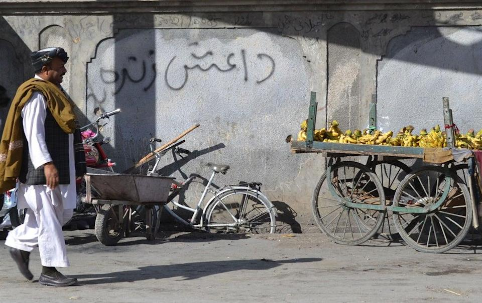 A Pakistani pedestrian walks past a wall graffiti which reads Daesh, the arabic acronym for Islamic State (IS), in Quetta  (AFP via Getty Images)