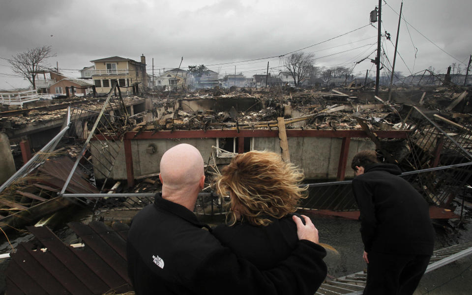 Robert Connolly embraces his wife, Laura, on Oct. 30, 2012, as they survey the remains of the home owned by her parents that burned to the ground in the Breezy Point section of New York. (Photo: Mark Lennihan/AP)