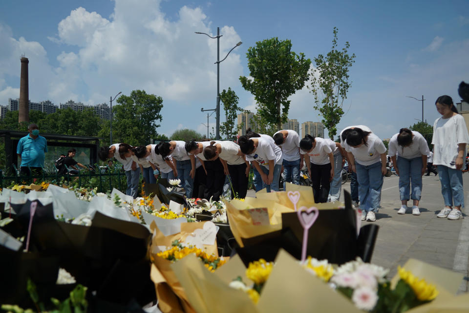 People bow to pay their respects outside the entrance to a subway station in Zhengzhou in central China's Henan Province, Tuesday, July 27, 2021. Residents laid flowers on Tuesday at the entrance of the subway station where more than a dozen people died after a record-breaking downpour flooded large swaths of Henan province in central China. (AP Photo/Dake Kang)