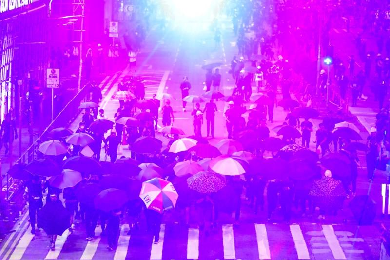 FILE PHOTO: Anti-government protesters protect themselves with umbrellas as they move toward riot police officers during a protest in Sham Shui Po district