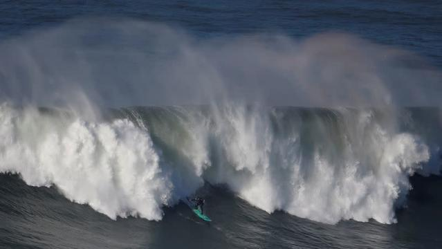 Portuguese surfer Alex Botelho drops in on a large wave at Praia do Norte in Nazare