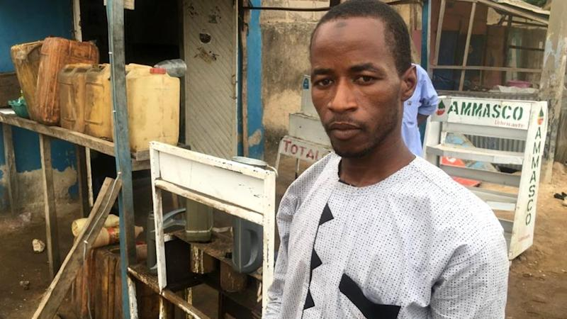 Former almajiri student standing in front of his gas shop