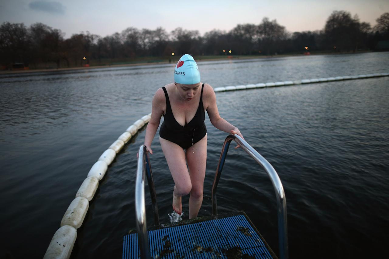 LONDON, UNITED KINGDOM - DECEMBER 13:  A woman climbs out of the Serpentine lake in Hyde Park after an early morning swim on December 13, 2012 in London, England. Extremely cold conditions are continuing to grip the UK with many overnight temperatures falling to -14C, bringing widespread ice, harsh frosts and freezing fog.  (Photo by Dan Kitwood/Getty Images)