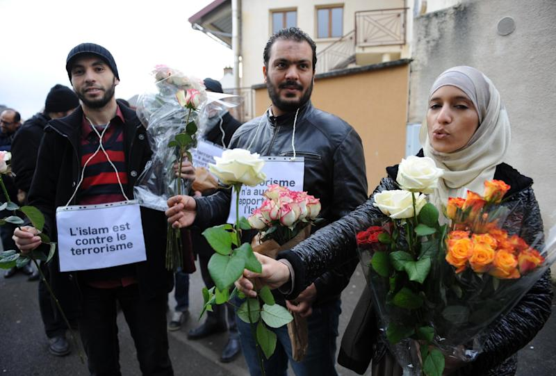 """Muslims with placards reading """"Islam is against terrorism"""" offer roses in the Sablons neighborhood of Le Mans on January 10, 2015 (AFP Photo/Jean-Francois Monier)"""