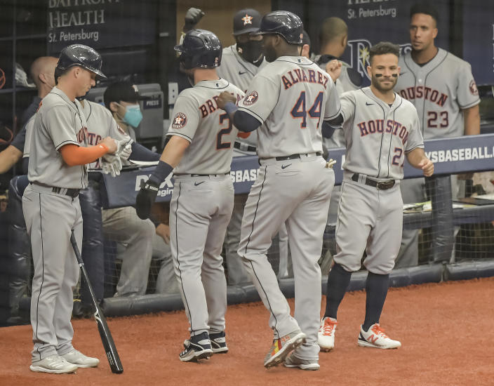 Houston Astros' Jose Altuve, right, greets Alex Bregman (2) and Jordan Alvarez (44) after they scored on Yulu Gurriel's bases-loaded single during the first inning of a baseball game against the Tampa Bay Rays Saturday, May 1, 2021, in St. Petersburg, Fla. (AP Photo/Steve Nesius)