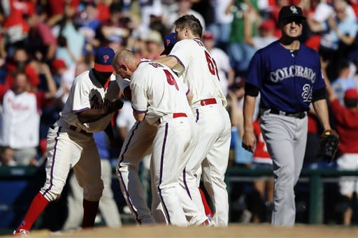 Philadelphia Phillies players celebrate with John Mayberry Jr., after his game-winning RBI single as Colorado Rockies first baseman Jordan Pacheco walks off the field in the ninth inning of the first game of a baseball doubleheader, Sunday, Sept. 9, 2012, in Philadelphia. Philadelphia won 3-2. (AP Photo/Matt Slocum)