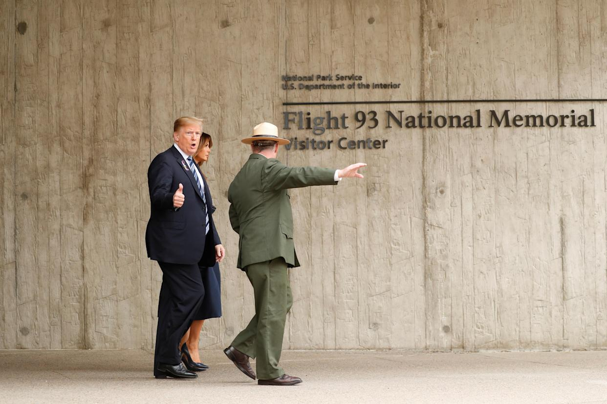 President Trump gives a thumbs-up to photographers as he and first lady Melania Trump walk with park superintendent Stephen Clark at the Flight 93 National Memorial near Shanksville, Pa., on Tuesday. (Photo: Kevin Lamarque/Reuters)