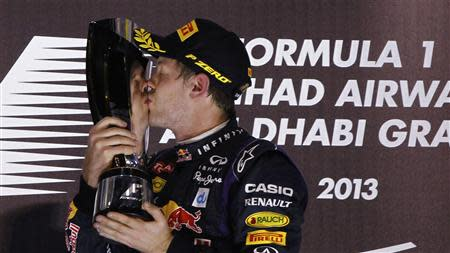 Red Bull Formula One driver Sebastian Vettel of Germany (C) kisses his trophy after winning the Abu Dhabi F1 Grand Prix at the Yas Marina circuit on Yas Island, November 3, 2013. Red Bull's four-times world champion Vettel won the Abu Dhabi Grand Prix on Sunday to chalk up his seventh successive victory and equal the longest winning streak in the modern era of Formula One. REUTERS/Caren Firouz