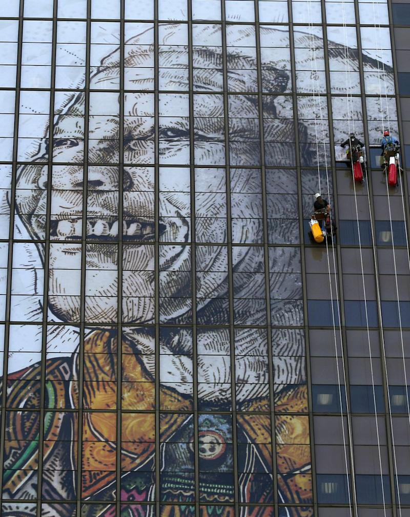 A portrait representing former president Nelson Mandela is installed on the windows of a building in downtown Cape Town, South Africa Thursday, June 13, 2013.  Mandela is spending a sixth day in the hospital and while there was no immediate update on his health Thursday, President Jacob Zuma on Wednesday reported that Mandela was responding better to treatment for a recurring lung infection.  (AP Photo)