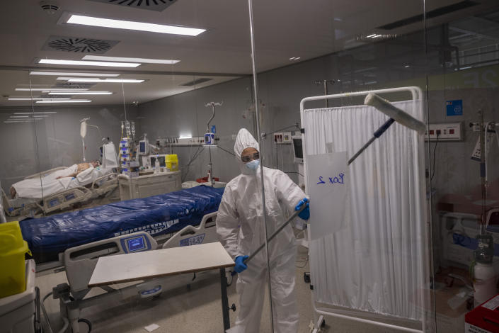 An employee of the new Nurse Isabel Zendal Hospital disinfects a box of the COVID-19 ICU ward in Madrid, Spain, Monday, Jan. 18, 2021. As the coronavirus curve of contagion turned increasingly vertical after Christmas and New Year's, the Zendal has been busy. On Monday, 392 virus patients were being treated, more than in any other hospital in the Madrid region. (AP Photo/Bernat Armangue)