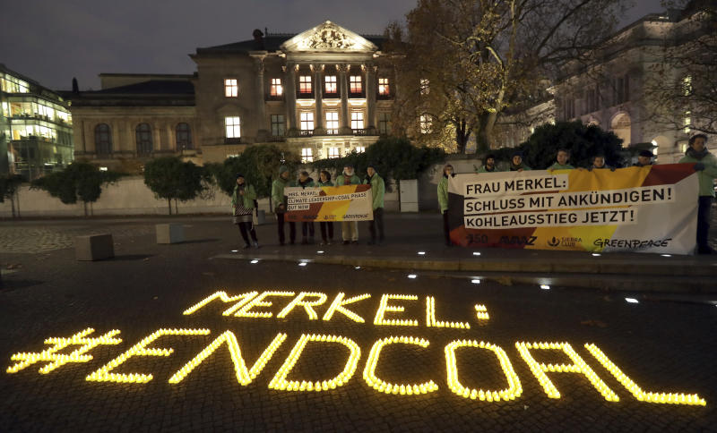 1,200 candles are placed by environmental activists, in front of a building close to the German federal parliament, a where German Chancellor Angela Merkel and other politicians meet for exploratory talks on a coalition between the German Christian Democratic Union Party (CDU), the Christian Social Union Party (CSU), the German Free Democratic Party, FDP, and the Green Party in Berlin, Germany, Tuesday, Nov. 14, 2017. (AP Photo/Michael Sohn)