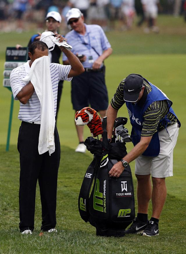 Tiger Woods wipes his face on the 10th hole during the second round of the PGA Championship golf tournament at Valhalla Golf Club on Friday, Aug. 8, 2014, in Louisville, Ky. (AP Photo/Mike Groll)