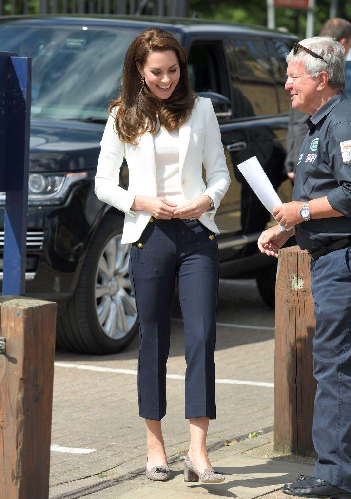 """<p>Kate arrived at the 1851 Trust Roadshow at the Docklands Sailing and Watersports Centre wearing a white shirt and Zara blazer, and J. Crew navy pants with gold button decals.</p><p><strong>More: </strong><a href=""""https://www.townandcountrymag.com/society/tradition/a10160941/kate-middleton-affordable-outfit/"""" rel=""""nofollow noopener"""" target=""""_blank"""" data-ylk=""""slk:Shop This Affordable Kate Middleton Look"""" class=""""link rapid-noclick-resp"""">Shop This Affordable Kate Middleton Look</a><br></p>"""