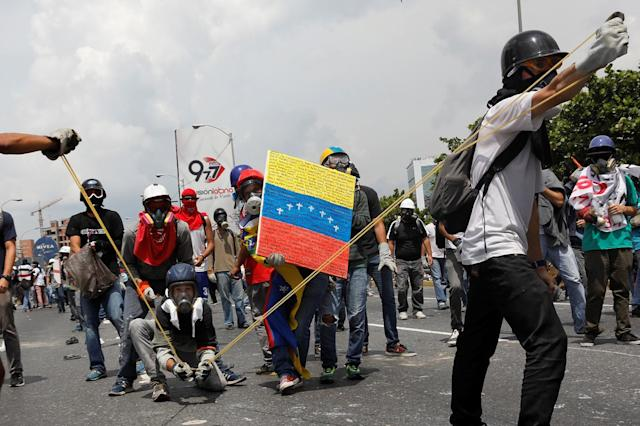 "<p>Opposition supporters uses a giant sling shot to throw a ""Poopootovs"", a bottle filled with feces, which is a play on Molotov, during a rally against President Nicolas Maduro in Caracas, Venezuela, May 10, 2017. (Photo: Carlos Garcia Rawlins/Reuters) </p>"